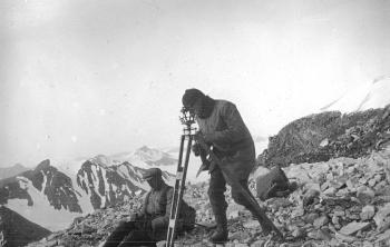 The expedition went back through the Matochkin Strait just before it refilled with drifting ice and continued their investigations along the west coast of the northern island. A small group of men climbed up a mountain to take topographic measurements from there. This picture, taken on the top of the mountain, features Olaf Holtedahl and Brynjulf Dietrichson.