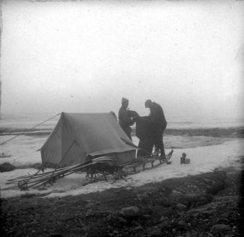 Reidar Holtedahl and Reidar Tveten packing up camp next to a medial moraine on the central plateau. The weather was quite mild, the snow was wet and heavy, and the stones from the medial moraine caused problems for the sledge. They ran into fog, but the group decided to continue, using the compass to navigate, rather than waiting for the weather to improve.